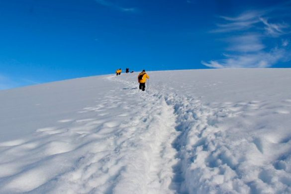 Three people walking in the snow in Antarctica