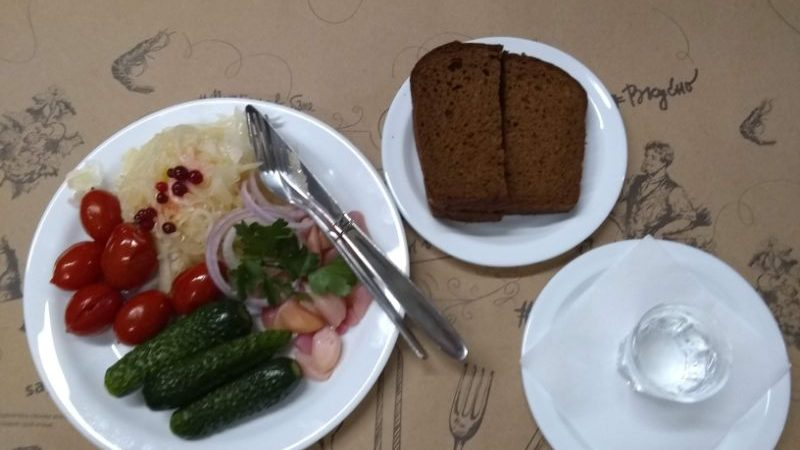 Plates filled with pickles, tomatoes, sauerkraut and dark rye bread