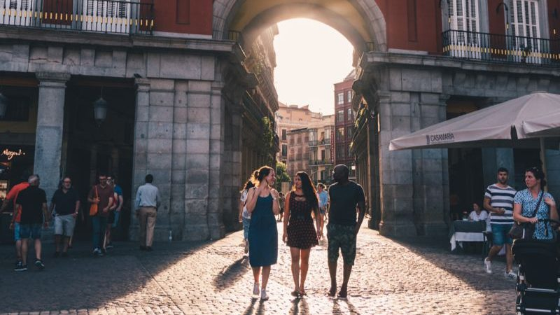 Three people walking into a square in Madrid at sunset