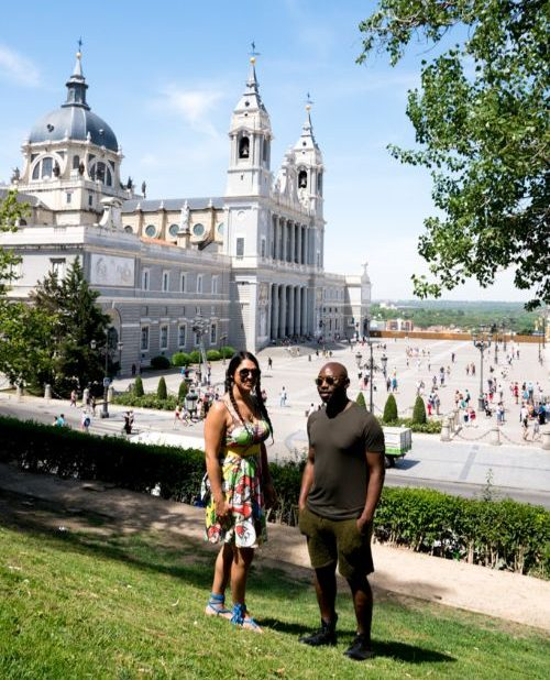 A man and a woman standing in front of a palace in Madrid