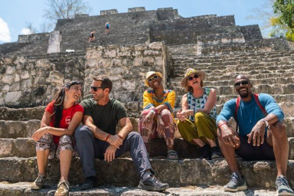 A group of travellers sitting at a ruin in Mexico