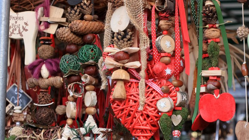 Wooden Christmas decorations hanging at a market stall.