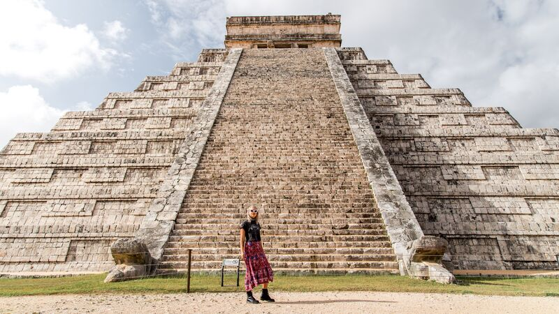 A female traveller standing in front of some ruins in Mexico