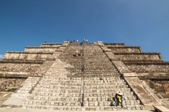 People sitting on the steps on an ancient ruin in Mexico