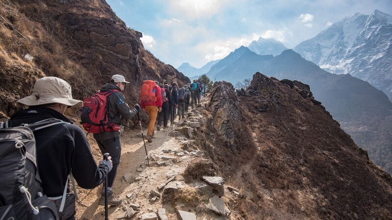 Hikers walking up a rocky path in Nepal