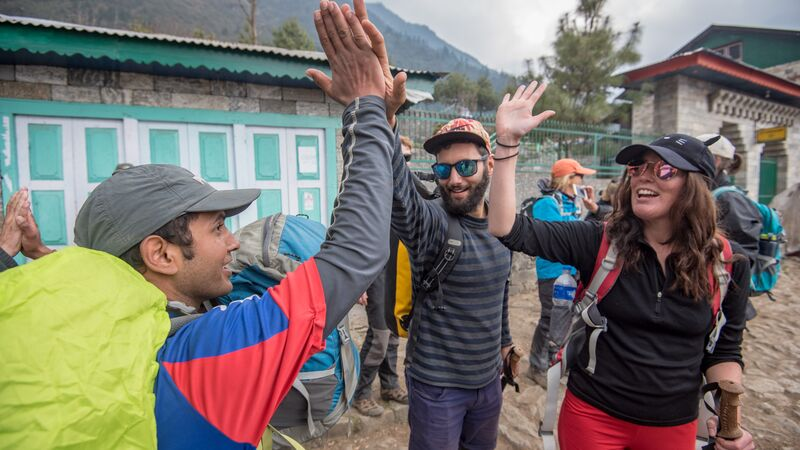 Two hikers high-fiving a local in Nepal.