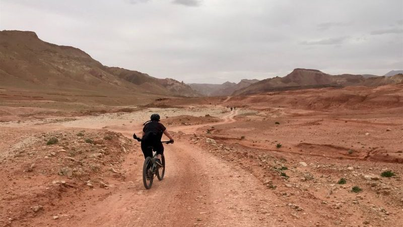 A woman cycles along a dirt road in the Moroccan desert.