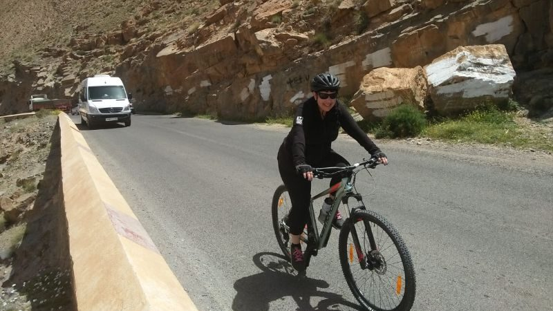A woman cycling up a steep hill in Morocco