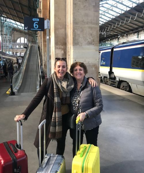 A mother and daughter with suitcases at a train station