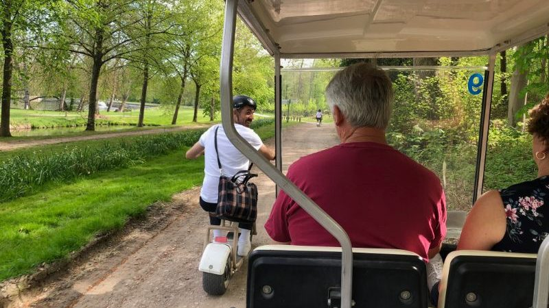 A man riding a bike past a golf buggy