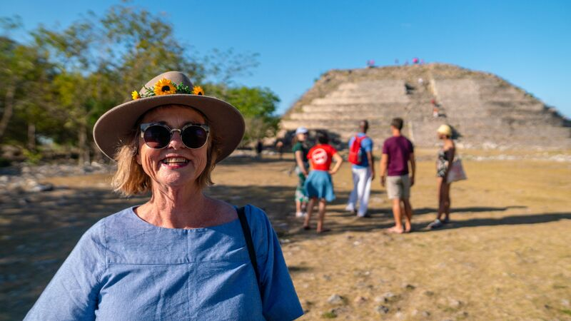 A woman in a blue shirt and a hat in front of a pyramid in mexico