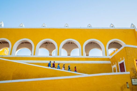 A group of people at a big yellow building in Mexico