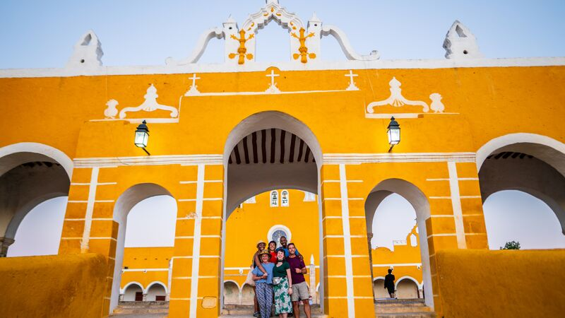 A group of travellers in front on a monastery in Izamal, Mexico
