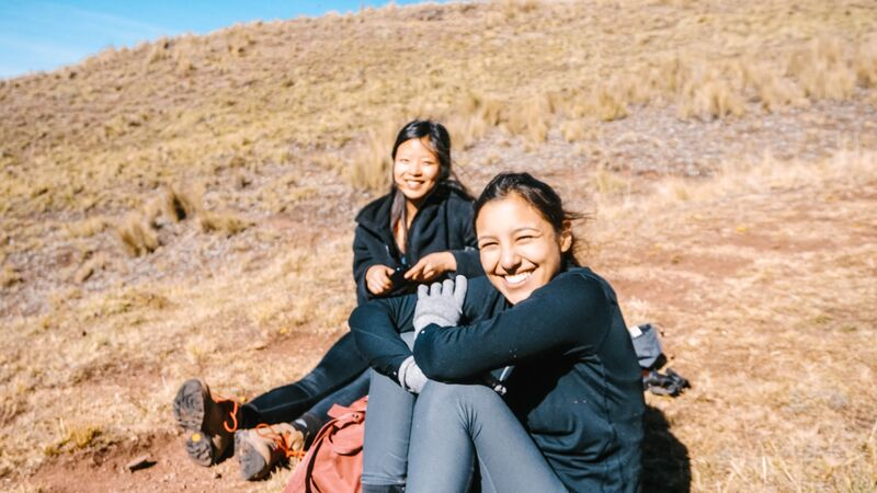 Two girls sitting in a field in Peru