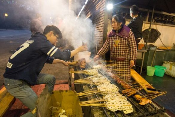 Two people working on a food stall on the street in China