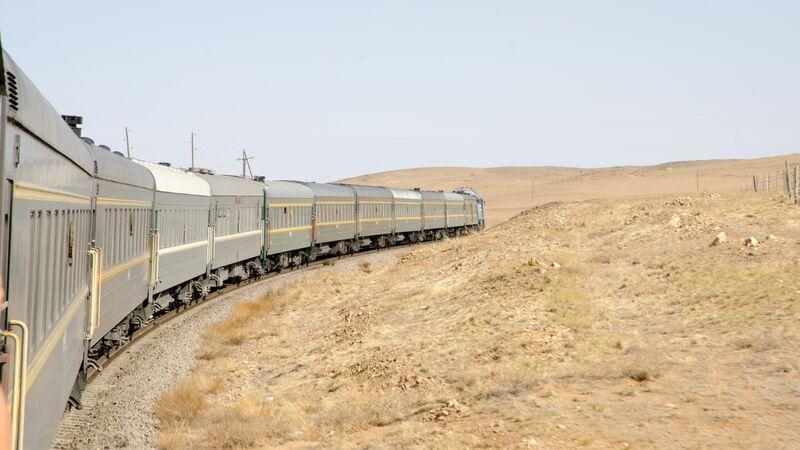 A train curls across the barren landscape in China
