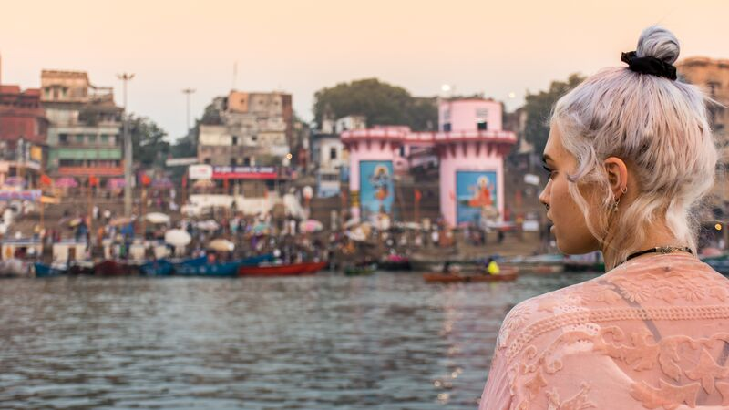A young woman looks out over the river in Varanasi