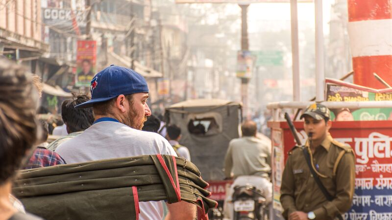 A man sitting in a rickshaw in a crowded street in India