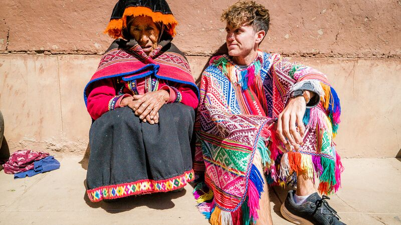 A young traveller in a traditional Peruvian costume sitting next to a local woman