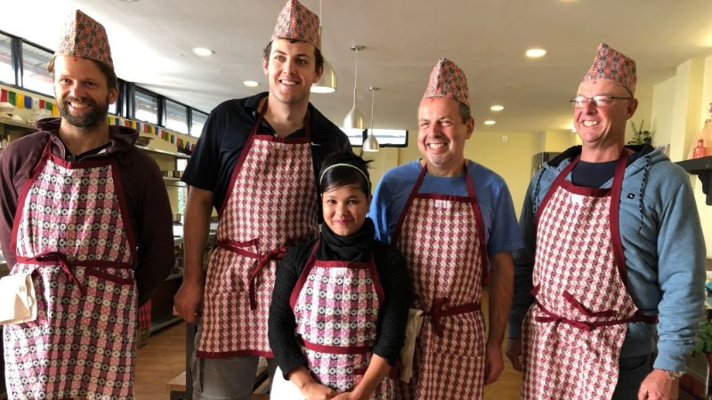 Four men and a women wearing red and white checked aprons