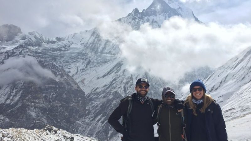 Three people surrounded by mountains in Nepal.