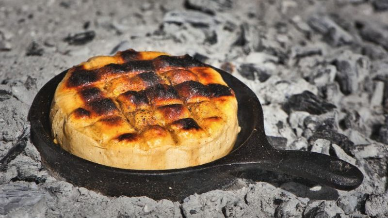 A small skillet of cheese sitting in a coal pit