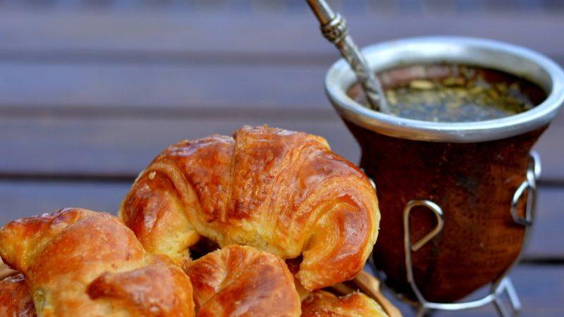 A plate of medialunas alongside a cup of tea