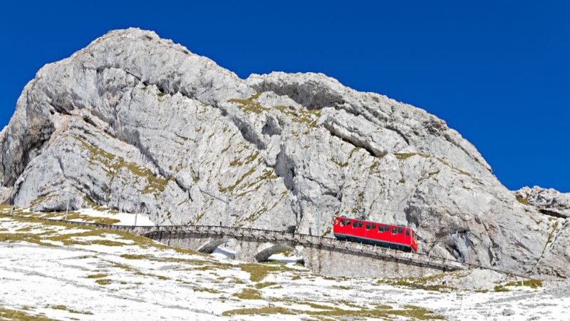 A small red train beside a large stony mountain