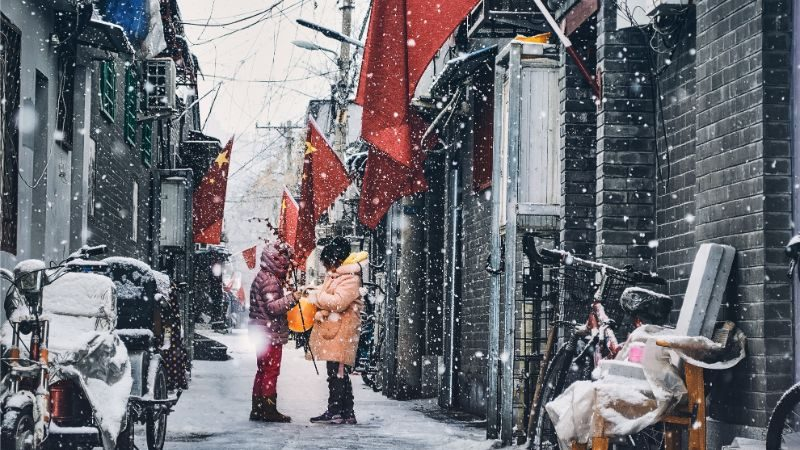 Two people standing in the snow in Beijing