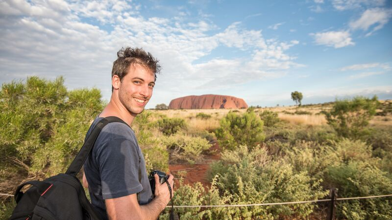 A young man smiling at the camera with Uluru in the background