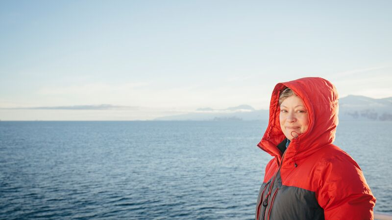 A woman in a red jacket smiling at the camera with the ocean behind her