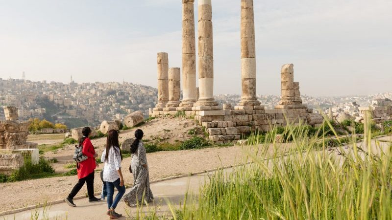 Travellers walking past some ruins in Jordan