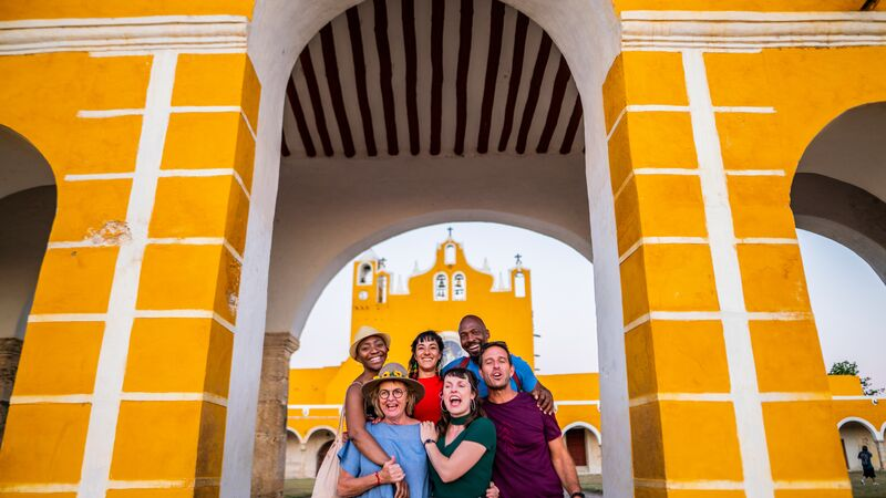 A group of travellers standing in front of a yellow building in Mexico