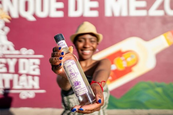 A woman holds a bottle of mezcal up to the camera