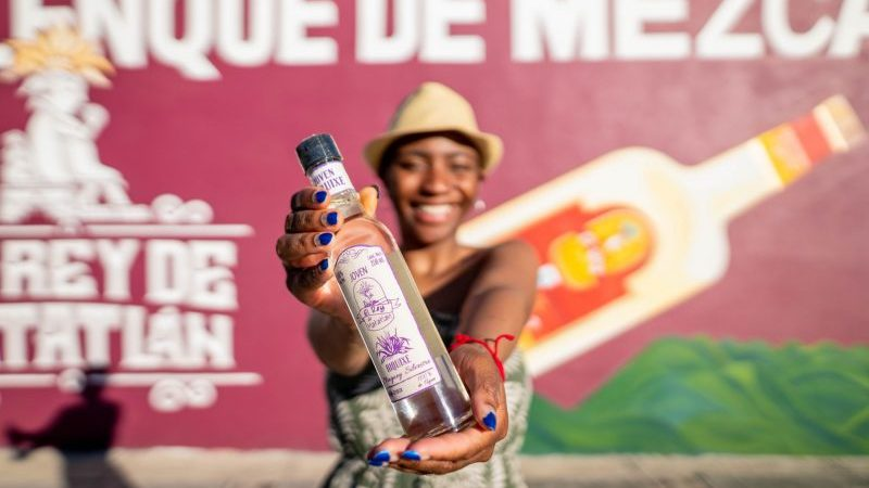 A young woman holds up a bottle of mezcal in Mexico