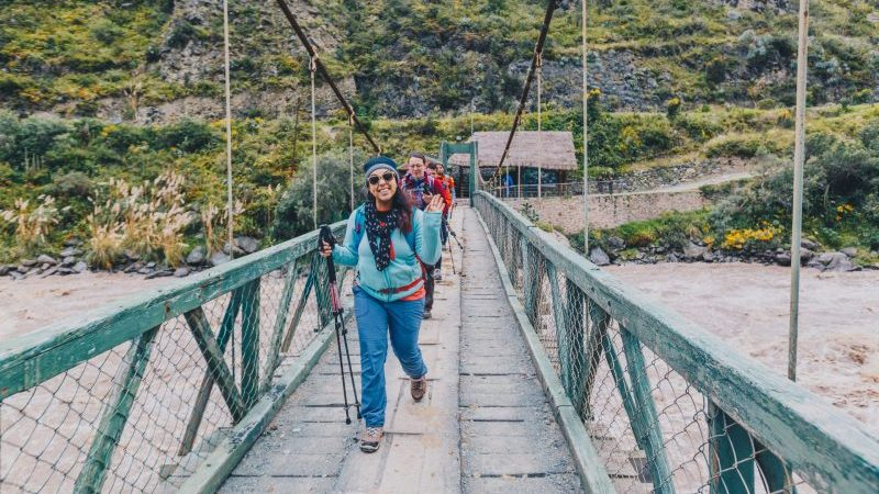 Hikers crossing a bridge in Peru