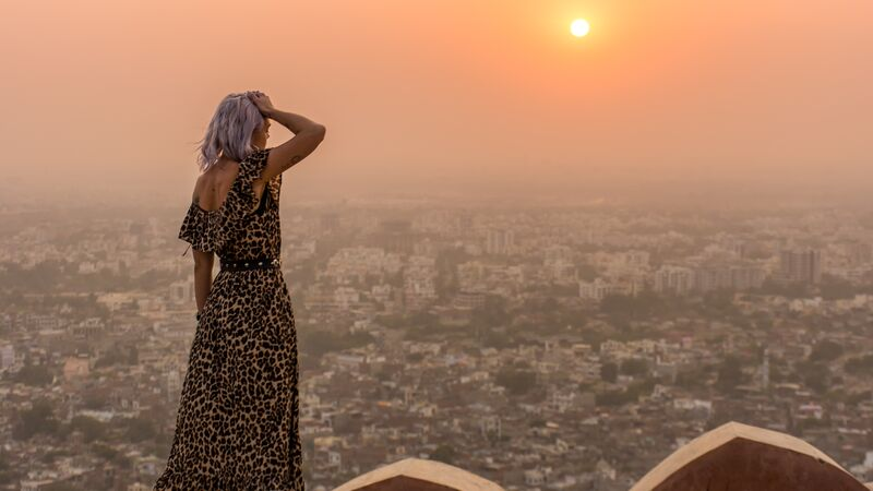 A woman looking at a view in India at sunset