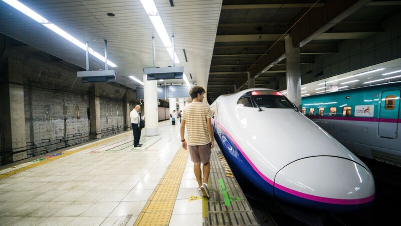 A young man getting onto a bullet train in Japan