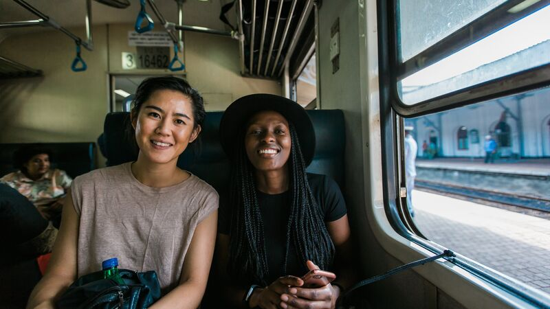 Two smiling women on a train in Sri Lanka