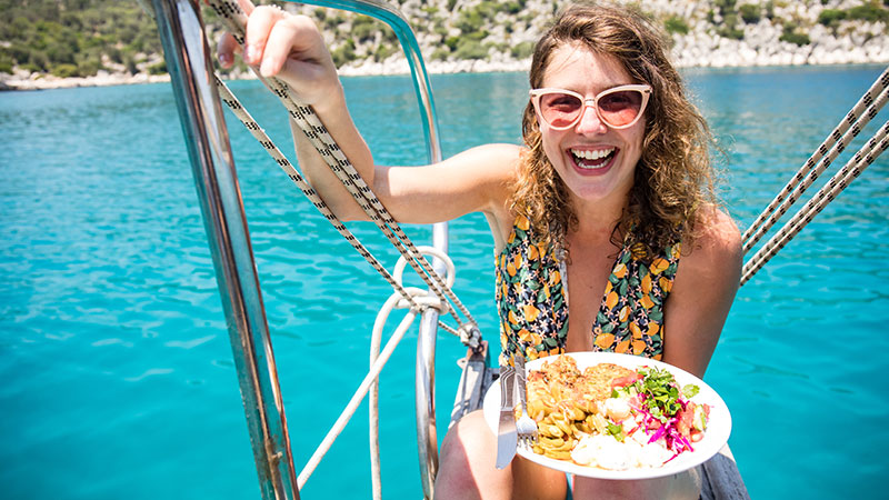 A smiling traveller on a boat holding up a plate of food