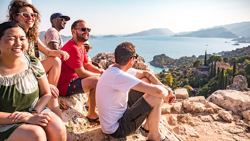 A group of travellers sitting on a rock in the sun in Turkey