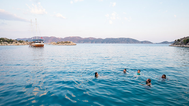 A group of travellers swimming in blue seas in Turkey