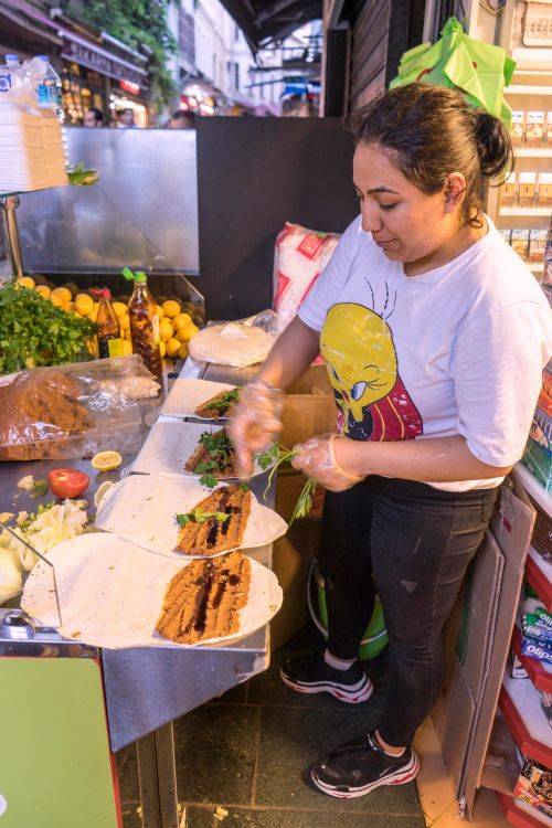 A woman prepares a traditional Turkish street food at a market