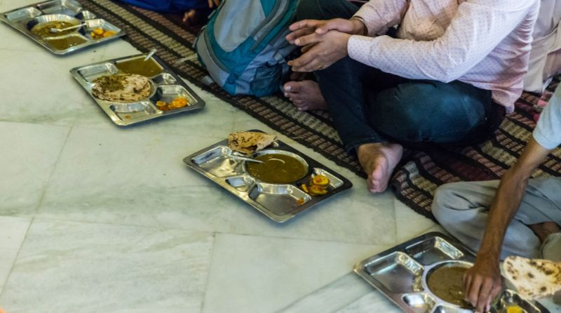 People sitting on the floor with plates of food at a temple in India