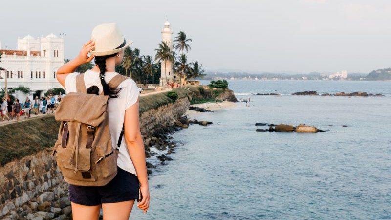 A woman wearing a hat and a backpack admiring the ocean and a lighthouse in Sri Lanka