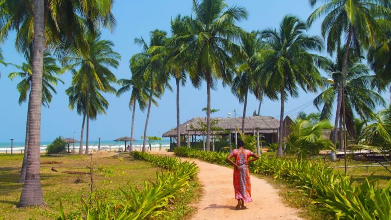a woman in a sari walking towards a beach.
