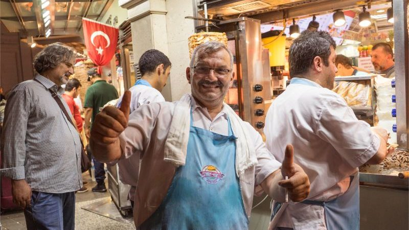 A man in a busy market giving a thumbs up to the camera
