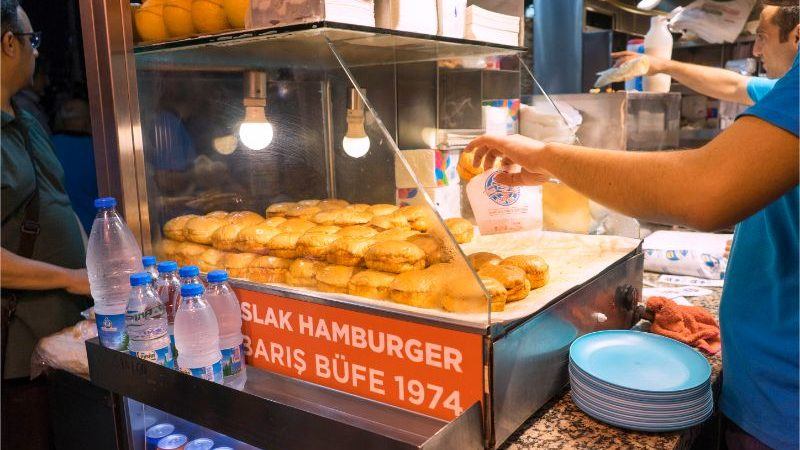 A vendor selling wet burgers in a Turkish market
