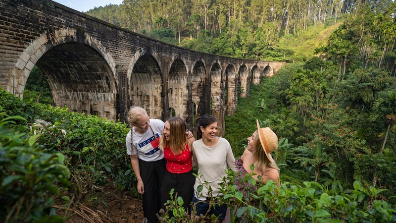 Four female travellers standing next to a beautiful arched bridge in Sri Lanka