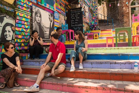 Travellers sitting on some brightly painted steps in Balat